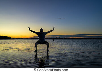 sunrise silhouette of a man standing in shallow water and practicing chigong or tai chi movements, Boyd Lake State Park in northern Colorado