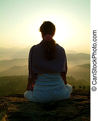 sunrise silhouette - woman meditating during sunrise on...