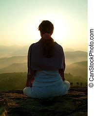 sunrise silhouette - woman meditating during sunrise on...