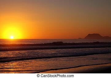 Sunrise over the surf on New Zealand beach