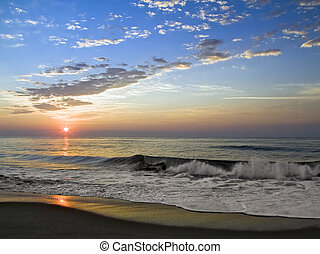 Sunrise Surf - The sun rises over sea surf with reflections...