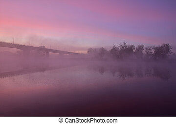 Sunrise, the outline of the bridge in the fog, a mysterious view.