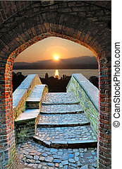 Sunrise seen over old stone bridge and through a medieval gothic archway.