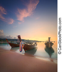sunrise with colorful sky and boat on the beach