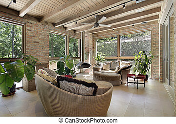 Sunroom with wicker furniture - Sunroom in luxury home with ...
