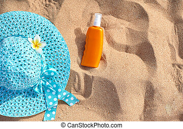sunscreen, hat on the sand, concept of summer vacation, an optic with a place for your text