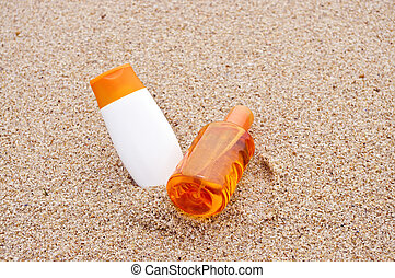Sunscreen in the beach - Two containers of sunscreen at the...