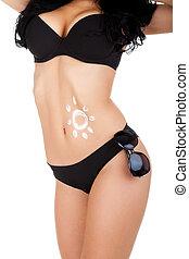 Sunscreen lotion over tan woman belly made sun shape,...