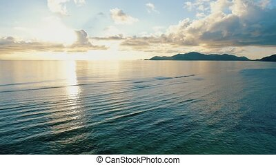 Sunset 4k footage over calm sea with tropical island silhouette on horizon. Flying the drone at low altitude over the ocean water