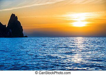 Sunset above blue sea