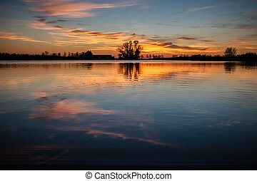 Sunset above lake in polder landscape with reflection in the water