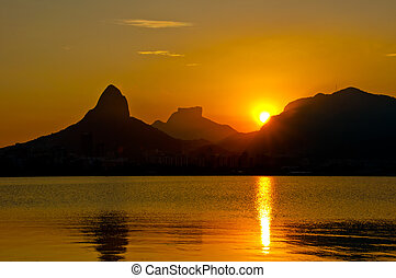 Sunset in Rio de Janeiro above mountains and Lagoa Rodrigo de Freitas.