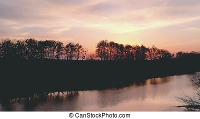 Sunset above river next to darkness