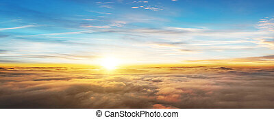 Sunset above the clouds, airplane view. Beautiful ladscape sky scenery with falling sun beneath horizon.