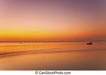 Sunset along the coast with bridge background