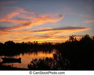 Sunset and Boat - Beautiful sunset over Bayou Liberty in...