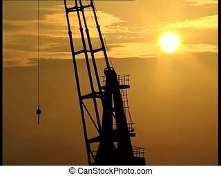 SUNSET and crane - Crane in a port at sunset, with a flaming...