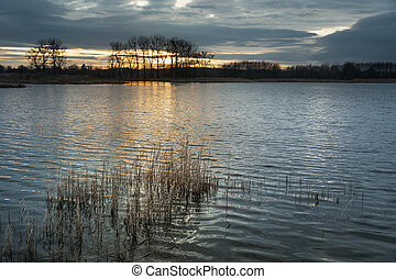 Sunset and dark clouds over the lake