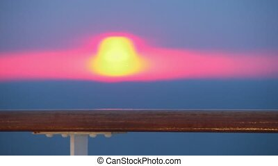 Sunset and handrail at deck of ship which sways on sea waves