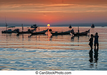 Sunset and longtail boats on tropical beach. Ko Tao island, Thai