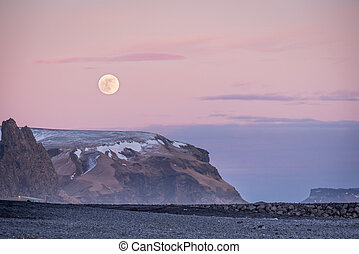 Sunset and moon rise over mountains and Vik?s black sand beach in Iceland