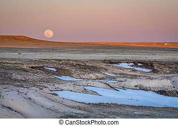 Sunset and moon rise over prairie