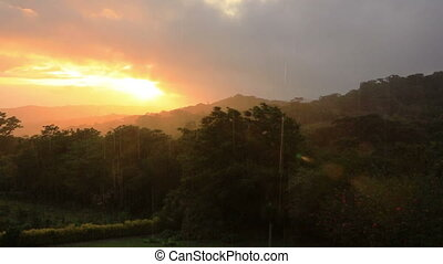 Sunset and rain over rainforest - View of sunset and rain at...