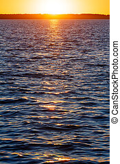 Sunset and sun track on lake surface.