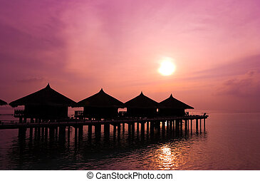 Sunset and water bungalows, abstract vacation background