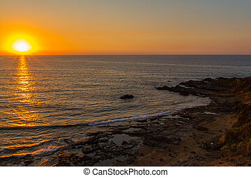 Sunset at a rocky beach in Pomos, Cyprus