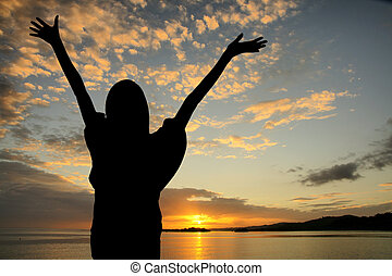 Sunset At Beach - Girl raising her hands during sunset at...