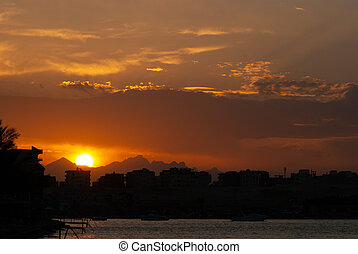 Sunset at city of Hurghada with buildings and mountains silhouette