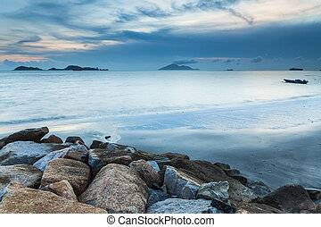 Sunset at coast with sea stones background