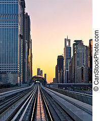 sunset at Dubai, UAE - Modern city at sunset, metro overpass...