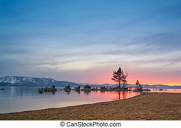 Sunset at Lake Tahoe with sand beach, mountains covered by...