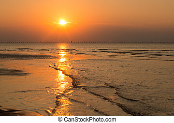 An orange sunset at low tide in Virginia Beach, Virginia with the Chesapeake Bay Bridge Tunnel at the horizon line in the distance.