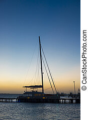 Sunset at marina with docked yacht and calm sea