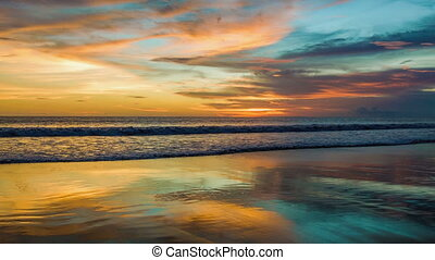 Colorful sunset at ocean with reflections on sand
