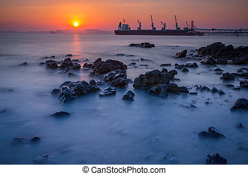Sunset at the beach with Cargo ship