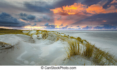 Sunset at the beach with dunes and clouds
