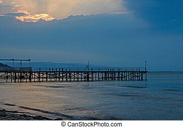 Sunset at the Black Sea shore from Albena, Bulgaria with golden sands, blue mystic water, seaside bridge
