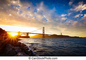 Sunset at the Golden Gate Bridge with sun starburst