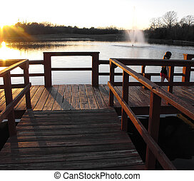 Sunset at the Lake - Child playing on dock at sunset at...
