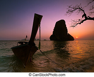 Sunset at tropical beach landscape with Thai traditional boat and tree. Rock formation island silhouette under evening sun at ocean coast . Pranang cave beach, Railay, Krabi, Thailand