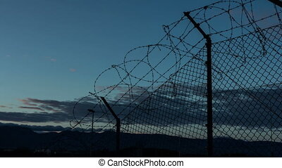 Sunset behind a barbed wire in prison.