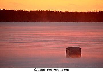 Sunset behind a fishing shack on Northern Saskatchewan lake