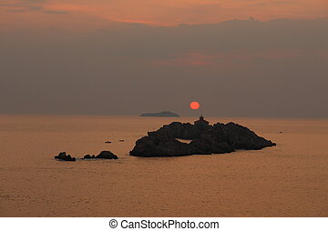 Sunset behind lighthouse on tiny island at mediterranean sea in Croatia
