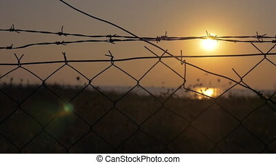 Sunset behind the barbed wire - Slow motion steadicam shot...