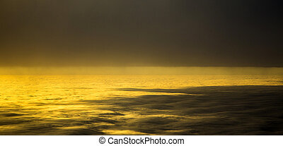 sunset between clouds with bright sun