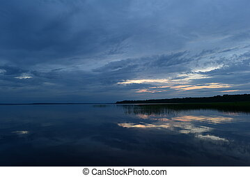 Sunset blue reflection on the lake water surface